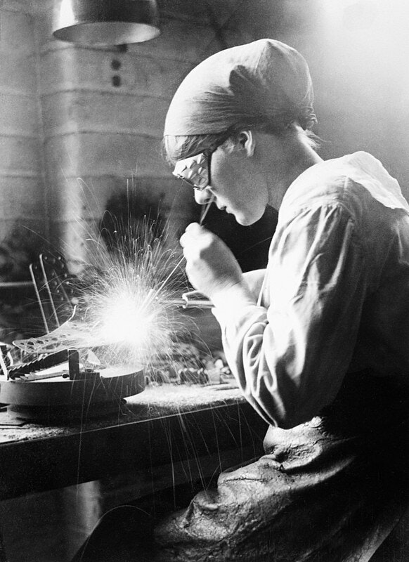A female acetylene welder at work in an aircraft factory in the Midlands, September 1918; photograph by George P. Lewis — Wikimedia Commons