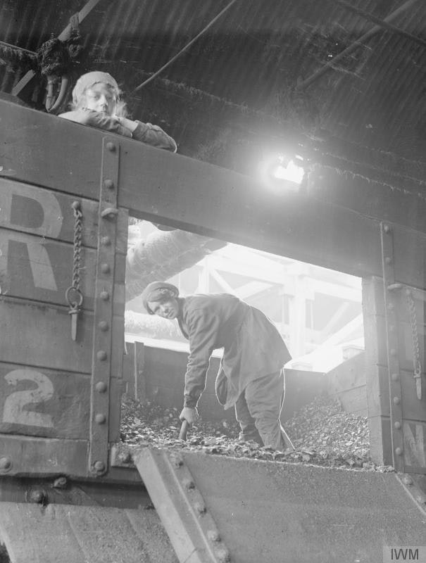 A female worker unloading coal from a railway waggon at the chemical works of Brunner Mond & Co. Ltd., Northwich, Manchester, September 1918; photograph by George P. Lewis — Wikimedia Commons